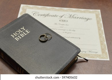 gold wedding rings with a bible and marriage certificate