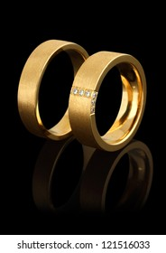 gold wedding rings with diamonds isolated on black background