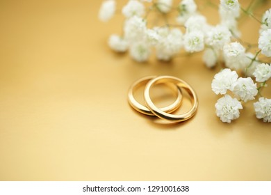 Gold wedding rings with flowers and lots of copy space for your text or invitation