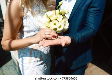 gold wedding rings in the hands of the brides with a white floral bouquet of flowers