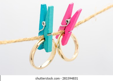Gold wedding rings hanging on rope with colored hooks