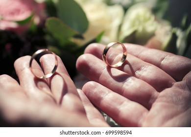 gold wedding rings in a man's hands