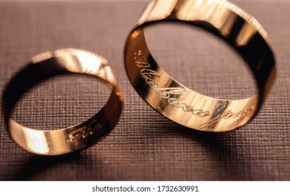 Gold wedding rings for newlyweds with an engraving inside. Close-up of rings on the table. Macro shooting of objects