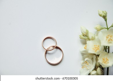 Gold wedding rings on a background of Jasmine flowers. Jasmine flowers in the form of a garland. Perfect for wedding invitations and greeting cards.