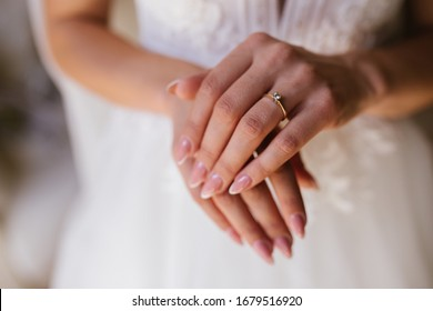 Gold wedding rings are on the bride's hand