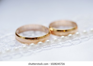 Gold wedding rings on a white fabric with lace and beads. Close-up.