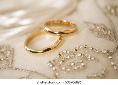 Gold wedding rings on a white cloth