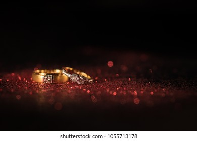 Gold wedding rings with red glitter and red bokeh on black background.