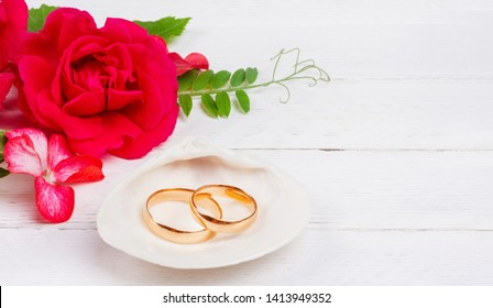 0a682d47f gold wedding rings in white seashell and red rose flowers on white wooden  background with copy