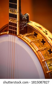 Gold & white banjo with strings and frets