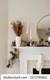 Gold and white Christmas decor on white mantle.