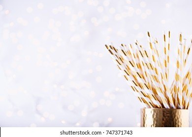 Gold and white paper straws in the golden glass. Christmas concept. Festive holiday party background. Horizontal