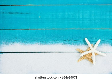 Gold and white starfish in sand border on antique rustic teal blue wood background; blank wooden beach sign with copy space
