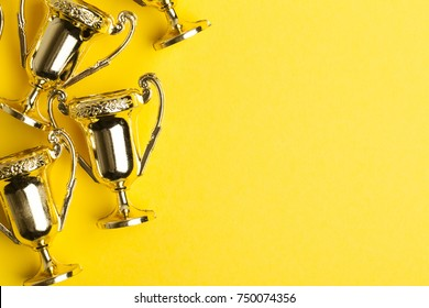 Gold winners achievement trophy on a yellow background