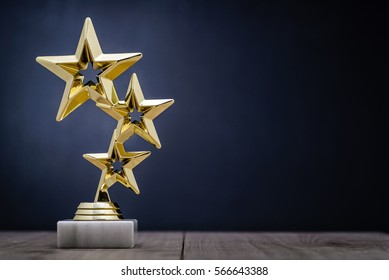Gold winners award with three stars to be awarded to the first place in a competition or championship standing on a pedestal against a blue background with copy space