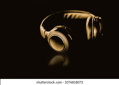 Gold Wireless Headphones on a black background Gold dark tone style.