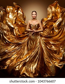 Gold Woman Flying Dress, Fashion Model in Waving Golden Gown, Fluttering Fabric Fly like Wings, Art Beauty Portrait