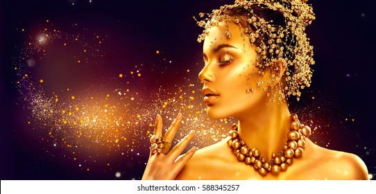 Gold Woman make up with golden shiny skin. Beauty fashion model girl with golden make up, hair and jewellery on black background. Gold earrings, ring and necklace. Metallic, glance. Hairstyle