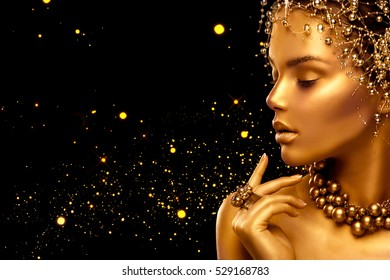 Gold Woman skin. Beauty fashion model girl with Golden make up, hair and jewellery on black background. Gold ring and necklace. Metallic, glance Fashion art portrait, Hairstyle and make up