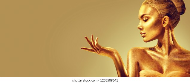 Gold Woman skin. Christmas Beauty fashion model girl with Golden make-up, hair and jewellery on gold background. Pointing hand, proposing products, sales. Metallic glance Fashion art portrait, glamour