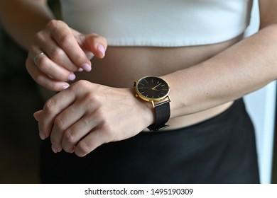 Gold women's wrist watch on the girl's hand