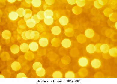 Gold and yellow Christmas Glittering background. Holiday abstract texture Festive background with defocused Golden bokeh