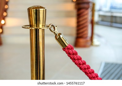 Gold-colored barrier with red cord in a luxurious foyer - close-up with selective focus