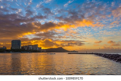 golde sunrise over diamond head crater landmark illuminates scattered clouds- taken from duke kahanamoku beach in waikiki hawaii Oahu