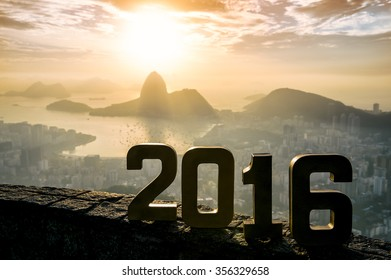 Golden 2016 sign standing at sunrise overlook view of Rio de Janeiro city skyline and Sugarloaf Mountain