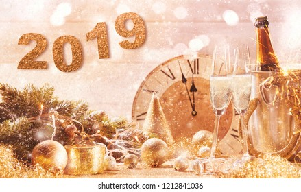 Golden 2019 New Years Eve party background with a clock counting down to midnight and flutes and a bottle of ice cold champagne with scattered decorations and sparkling background bokeh