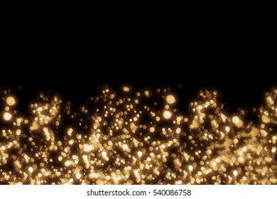 Golden abstract sparkles or glitter lights. Merry Christmas festive background.defocused circle bokeh or particles