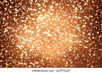Golden abstract sparkles or glitter lights. Festive gold background. Defocused circles bokeh or particles. Template for design