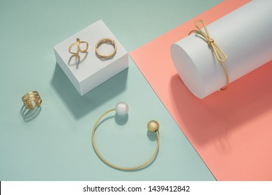 Golden Accessories set bracelets and rings on pink and blue background