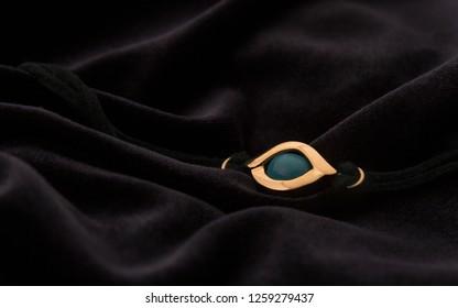 Golden amulet eye pendant  bracelet on velvet dark fabric