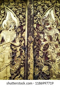 """Golden antique carving Thai pattern or Lai Thai """"Thep Pha Nom"""" decorated on the old wooden door of a building in Thai temple."""
