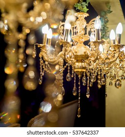 Golden antique chandelier on black background