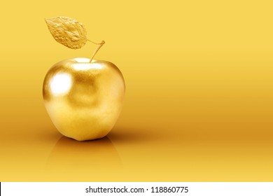 Golden apple on yellow background.