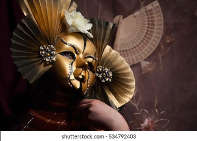 Golden asian mask close view. Woman in asian style golden carnival mask posing in orange dress with fan & flowers background.
