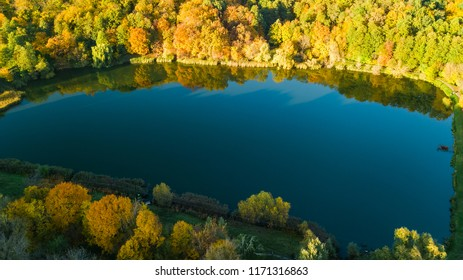 Golden autumn background, aerial drone view of forest with yellow trees and beautiful lake landscape from above, Kiev, Goloseevo forest, Ukraine