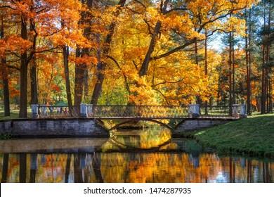Golden Autumn in Catherine Park, Tsarskoye Selo. The city of Pushkin, Leningrad region. Metallic bridge with reflections in the water on a bright sunny day.