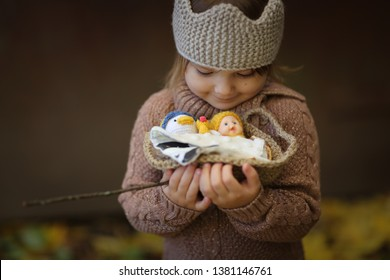golden autumn and a girl child with a basket of toys, a girl in a knitted crown and sweater, cozy warm autumn