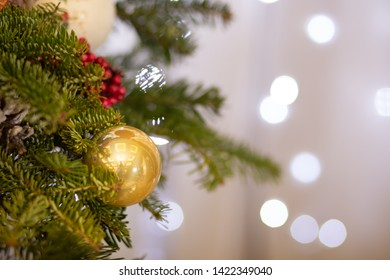 Golden ball Christmas ornament hanging on dry tree branch. Shining garland golden lights. Magical atmosphere. Macro photo of golden ball and light garland on Christmas tree