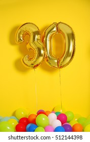 Golden balloons for 30th birthday celebration on yellow wall background