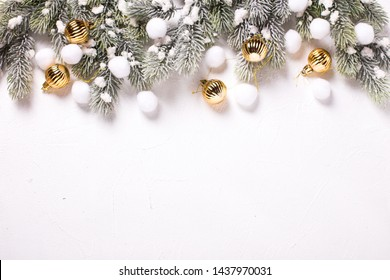 Golden balls and branches fur tree on texture white  background. Decorative christmas composition. Selective focus. Place for text. Flat lay.