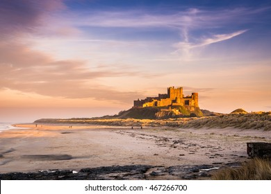 Golden Bamburgh Castle / Bamburgh Castle on the Northumberland coastline, bathed in late afternoon golden sunlight