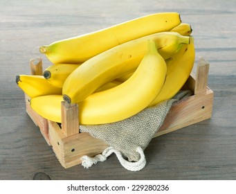 golden banana in crate on rustic table