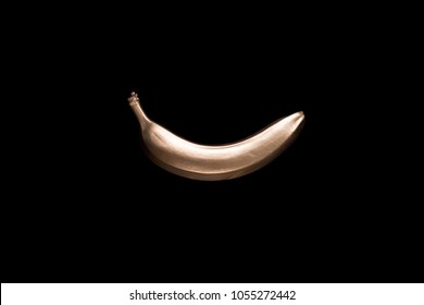 Golden banana on a black background. Creative concept with fruit.