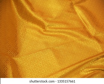 Golden Banares silk sari spread out in front of customers in a textile shop. These saris are famous for their gold and silver zari, brocade.