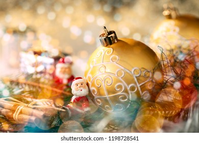 Golden bauble with Christmas decoration and little figure as Santa Claus