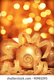 Golden baubles Christmas tree ornament, winter holidays decoration, ornamental decorative border, toys over gold background with magic glowing blur bokeh lights, new year eve